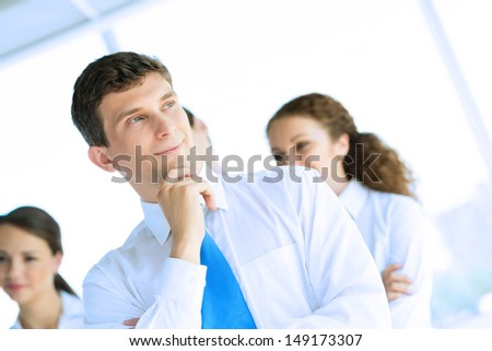 young successful businessman is thinking outside the flipchart, a number of his colleagues, teamwork - stock photo