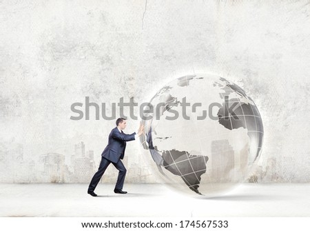 Young successful businessman pushing Earth planet ball - stock photo