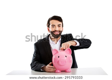 Young successful businessman putting a coin to piggybank. - stock photo