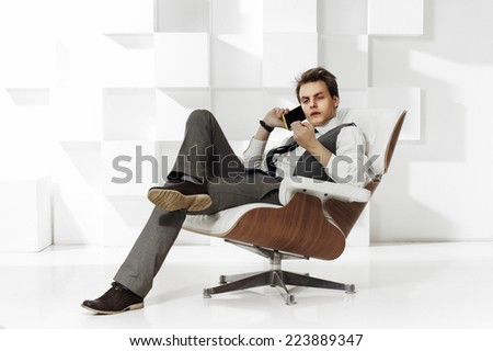 young successful businessman sitting in expensive armchair and talking on mobile phot. Fashion style portrait in modern office interior - stock photo