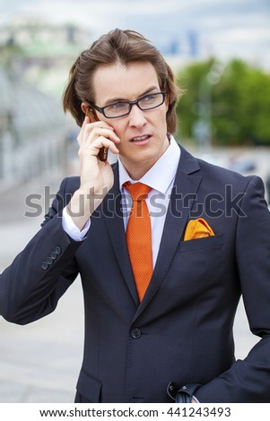Young successful businessman talking on his cell phone on the street, summer outdoors - stock photo
