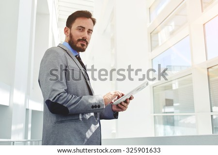 Young successful businessman using his touch pad while standing in modern office building inside, intelligent men entrepreneur in luxury suit holding digital tablet while resting during work break  - stock photo
