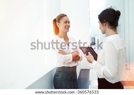 Young successful female office worker holding touch pad to search for the right information while talking with colleague before briefing, two women using digital tablet to work together on meeting  - stock photo