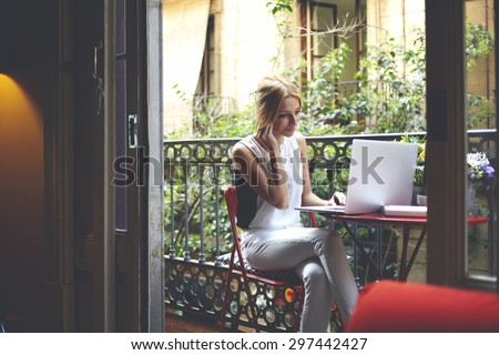 Young successful freelancer girl work on her laptop while sitting at home balcony, intelligent attractive female student using computer for browse Internet and listen to music with headphones     - stock photo