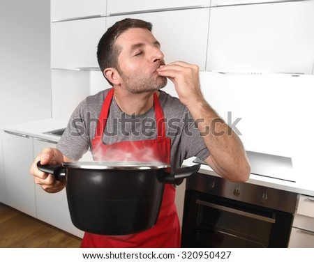 young successful man at home kitchen in red cook apron holding pot delighted with the good smell and taste of his dish enjoying the delicious aroma in delightful face expression and gesture - stock photo