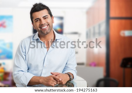 Young successful man at office - stock photo