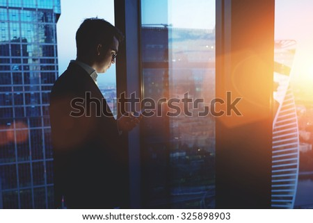 Young successful man entrepreneur mobile phone while standing in skyscraper office interior at sunset, intelligent male professional worker holding digital tablet while resting after business meeting - stock photo