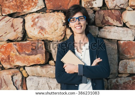 Young successful smiling woman wearing glasses standing outdoor crossing arms, holding a notepad and pen leaning on a rock wall. Pioneer woman at work. Eye level bussinesswoman success story portrait. - stock photo