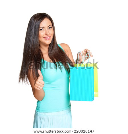 young sun-tanned woman  dressed in a turquoise shirt   holding colorful paper bags, showing thumb UP and smiling at the camera, isolated on white background - stock photo