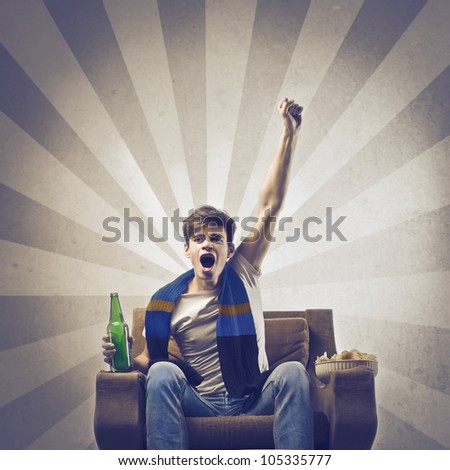 Young supporter triumphing on an armchair - stock photo