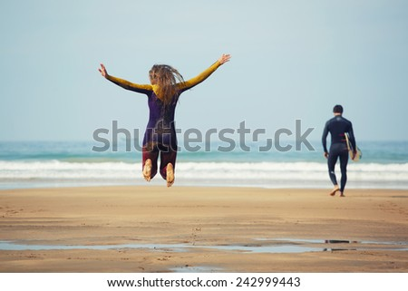 Young surfer girl jump having fun while her friend walk to the ocean ready to surfing - stock photo