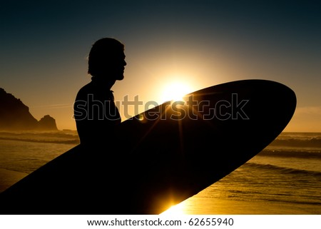 Young surfer on the beach with his surf board beside, looking at the ocean - stock photo