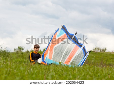 Young surfer preparing windsurfing sail on the grass - stock photo