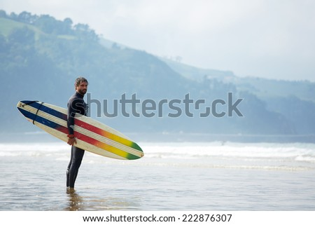 Young surfer standing agains the ocean looking the waves, professional surfer in black wetsuit holding with one hand big beautiful surfing board with multi-colored stripes, sunny day on ocean beach - stock photo