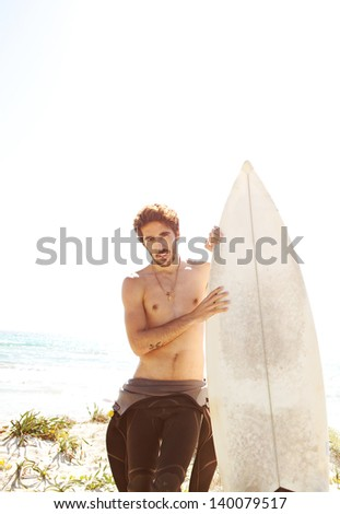 Young surfer standing on a white sand beach dunes, holding his surfing board and getting ready for surfing while wearing neoprene rubber suit during a sunny day. - stock photo