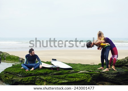 Young surfers having a good time waiting waves on beautiful surf spot standing against the ocean, couple having fun on a beach with a friend sitting next to them near his surfboard - stock photo