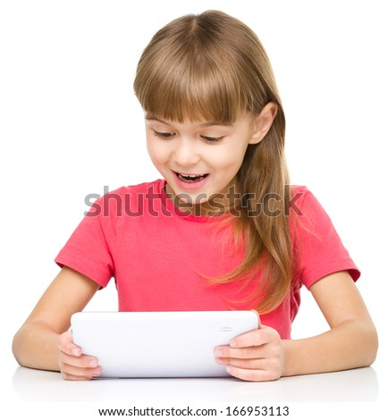Young surprised girl is using tablet while sitting at table, isolated over white - stock photo