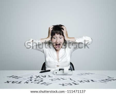 Young surprised woman at her desk frightened by taxes shouts out holding hands on  her head - stock photo