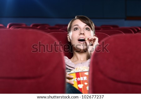 Young surprised woman eating popcorn in the movie theater - stock photo