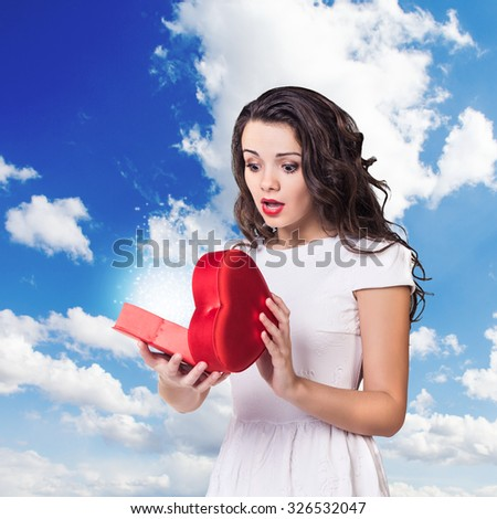 Young surprised woman holds open heart box on the sky background - stock photo