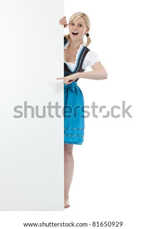 Young surprised woman in dirndl pointing with finger at blank sign. Isolated on white background. - stock photo