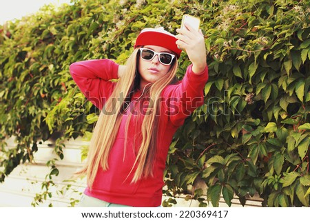 Young swag girl taking a selfie outdoors on sunny summer day. Photo toned style Instagram filters - stock photo