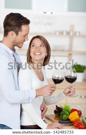Young sweet couple drinking red wine in the kitchen - stock photo