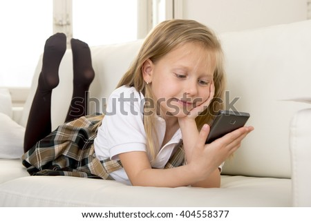young sweet cute and beautiful 6 or 7 years blond old girl in school uniform lying on home sofa couch using internet app on mobile phone playing online game looking happy and relaxed - stock photo