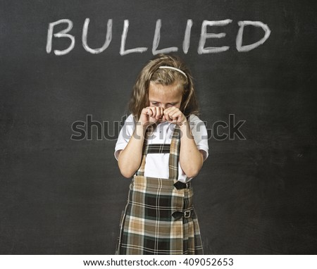 young sweet junior schoolgirl victim of bully crying sad standing in front of school class blackboard with chalk text bullied in school children bullying problem and education stress concept - stock photo