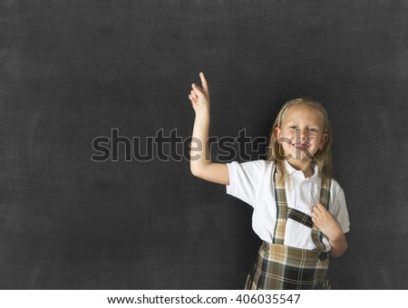 young sweet junior schoolgirl with blonde hair standing and smiling happy pointing to copy space on class blackboard wearing school uniform in children education success and fun - stock photo