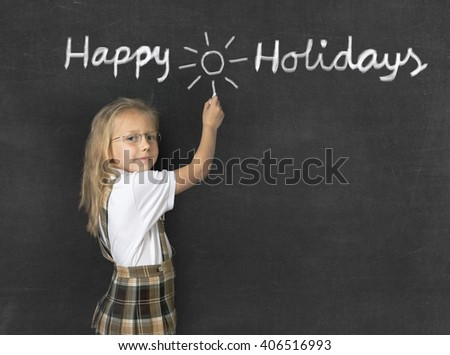 young sweet junior schoolgirl with blonde hair standing happy and smiling writing with chalk happy holidays drawing a sun in classroom blackboard wearing school uniform - stock photo