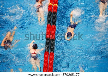 Young Swim team warming up in the pool, some motion blur on swimmers - stock photo