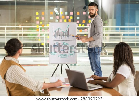Young talented man showing to his colleagues new business strategy. - stock photo