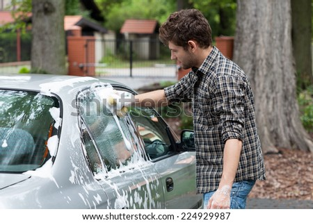 Young tall man washing his silver car - stock photo
