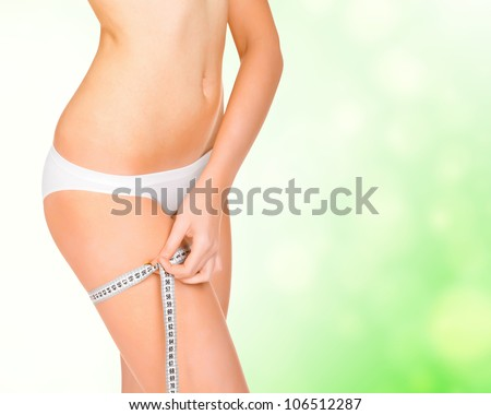 Young tanned woman measuring her body, green blurred background - stock photo