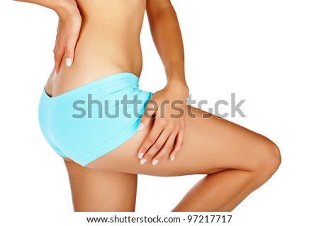 Young tanned woman with beautiful sporty buttocks and slim waistline - isolated on white wearing blue shorts style underwear - stock photo