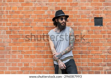 Young tattooed man portrait against brick wall in Shoreditch borough. London, UK. Hipster style - stock photo