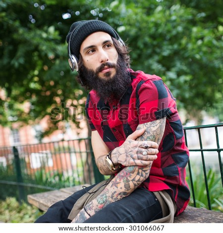 Young tattooed man portrait with head phones in a park in Shoreditch borough. London, UK. Hipster style. - stock photo