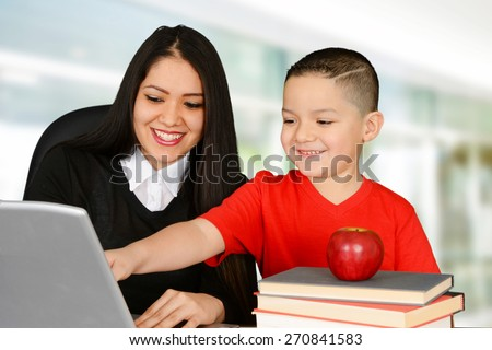 Young teacher and her pupil looking at laptop - stock photo