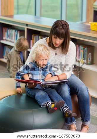 Young teacher and schoolboy reading book in library - stock photo