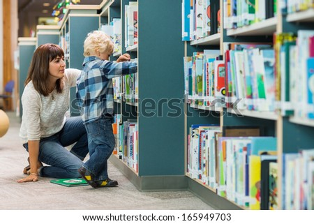 Young teacher assisting boy in selecting book from bookshelf in school library - stock photo
