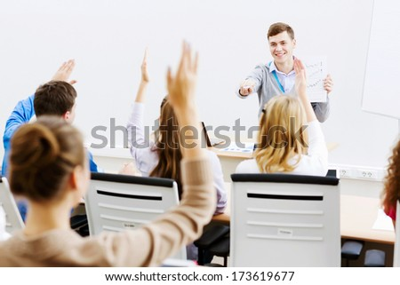Young teacher in classroom standing in front of class - stock photo