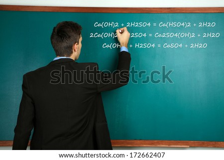 Young teacher near chalkboard in school classroom - stock photo