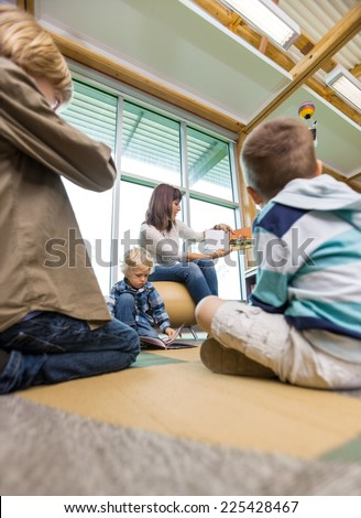 Young teacher showing picture book to children in school library - stock photo