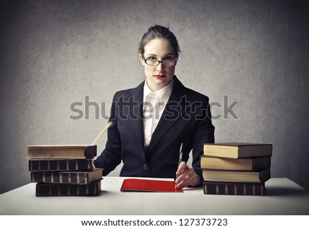 young teacher sitting at desk with books - stock photo