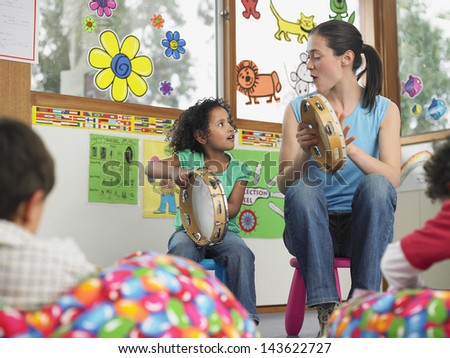 Young teacher with girl playing music in classroom - stock photo