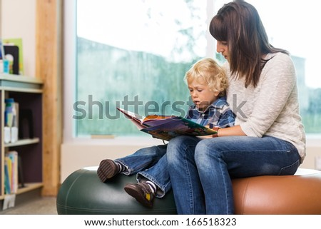 Young teacher with schoolboy reading book in library - stock photo
