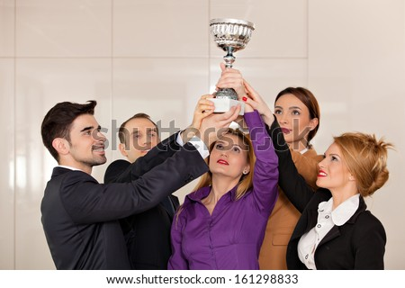 young team holding a trophy; happy business people celebrating their victory - stock photo