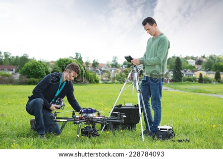 Young technicians working on UAV spy drone in park - stock photo