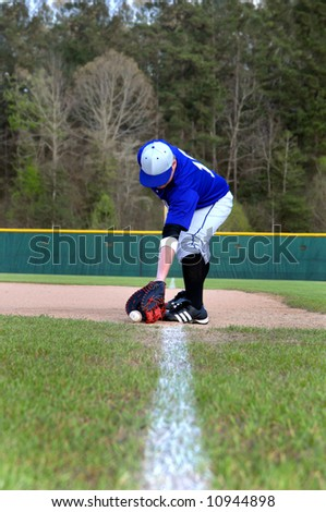 Young teen baseball player catches a line drive to first base.  Line stretches to first base. - stock photo